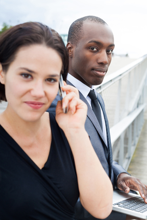 collaborators: Business people working outdoors, woman phoning and man on laptop Stock Photo