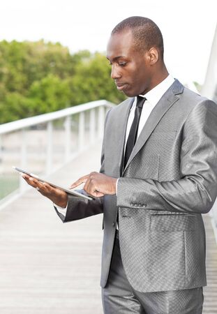 businessman standing: Portrait of a businessman working on electronic tablet