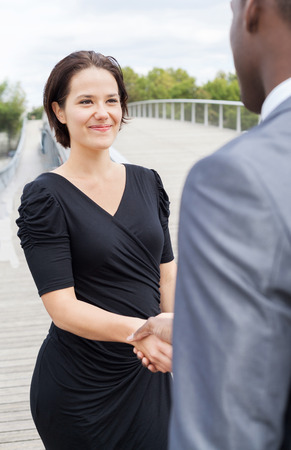 collaborators: Beautiful businesswoman and or businessman client handshaking