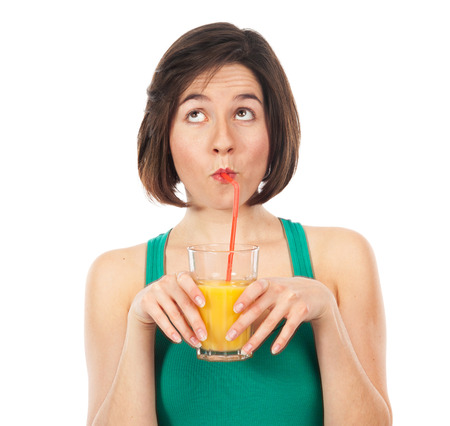 drinking straw: Portrait of a young woman drinking an orange juice with a straw, and looking up isolated on white Stock Photo