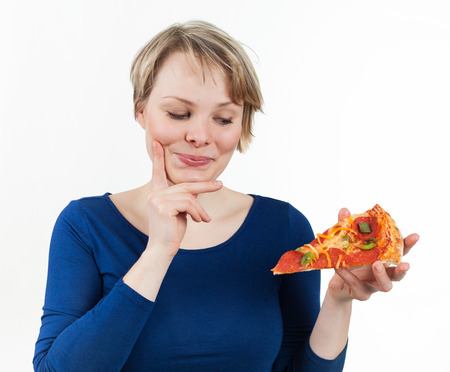 Young woman looking at a piece of pizza with appetite, isolated on white Archivio Fotografico