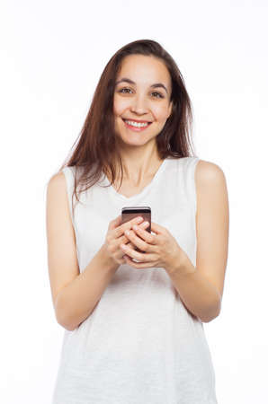 Young woman using her phone and looking at the camera, isolated on white