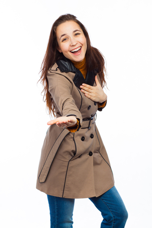 Young and funny woman standing up and wearing a coat, isolated on white