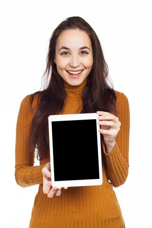 Young brunette displaying a blank touchpad and having a funny expression, isolated on white