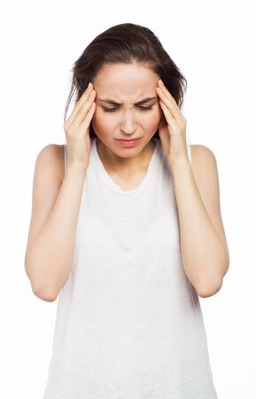 Young woman suffering of a headache and touching a head, isolated on white