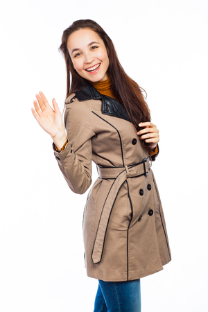 Young happy woman waving her hand to say bye or hello, isolated on white