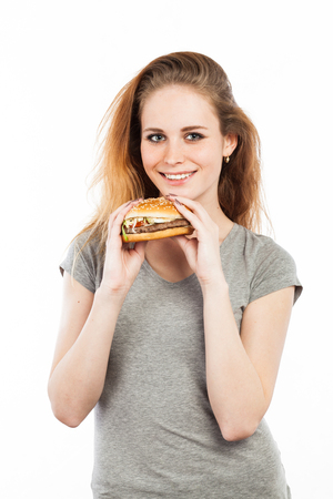 Portrait of a cute young woman with a big burger, isolated on white