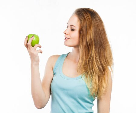 Portrait of a beautiful girl holding a green apple, isolated on white Standard-Bild