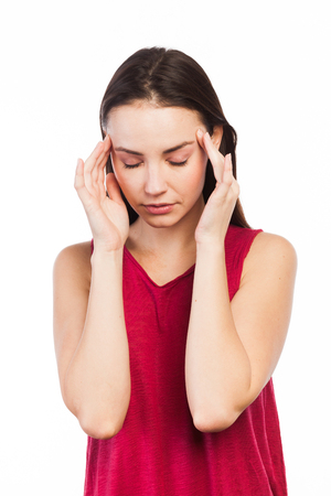 Portrait of a young woman having a headache, isolated on white