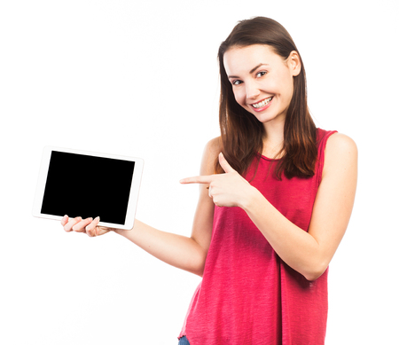 Smiling woman holding and showing the blank screen of an electronic tablet, isolated on white