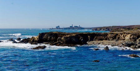 byway: Piedras Blancas Lighthouse in the background with the Elephant Seals in the foreground Stock Photo