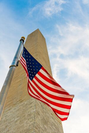 Looking at the Washington Monument from below with the American Flag featured infront