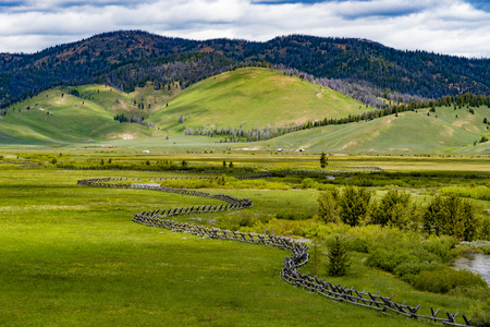 A rural scene featuring farmland and fencing with a mountain in the background. Taken along the Sawtooth Scenic Byway in Idaho
