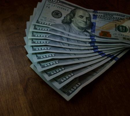 100 Dollar Bills Isolated on Wood Background