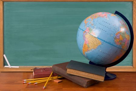 knowing: Old school books on a desk with a globe in front of a green chalkboard