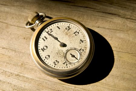Antique pocket watch clock in sepia tone on a wood floor