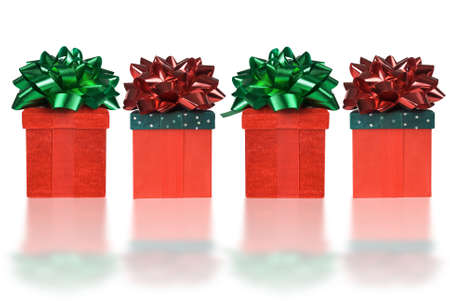Gifts wrapped in red and green material with colorful ribbons with a reflection Stock Photo - 1991156