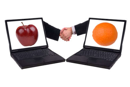 laptop computer with business handshake and apples and oranges isolated on a white background photo