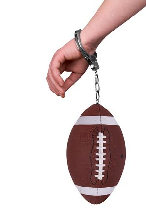 One hand handcuffed to a football isolated over white photo
