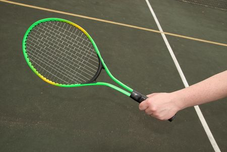 green tennis racket in a womans hand in front of a tennis court