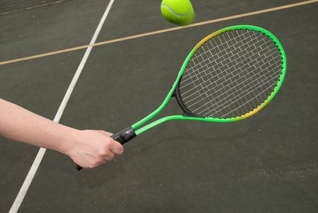 tennis ball in mid-flight with woman's hand and green racket Imagens - 2110712