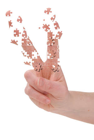 deconstruct: Peace sign hand breaking up into puzzle pieces over white