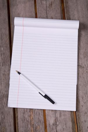 White lined legal notepad and a pen on a wood picnic table