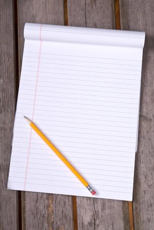 White lined legal notepad and a pencil on a wood picnic table.