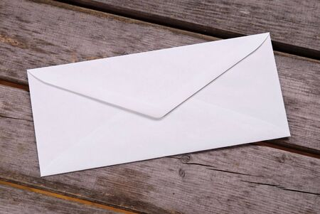 Plain white envelope on a wood picnic table