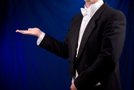 entertainers: Man in Tuxedo with open hand over a stage lit background