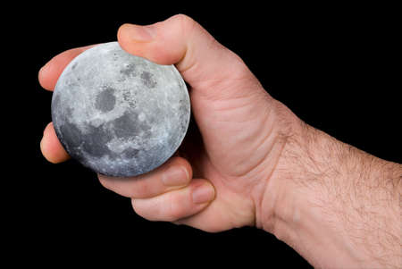 The Earths moon held by a mans hand isolated over black
