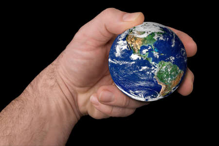 The earth held by a mans hand isolated over black Imagens