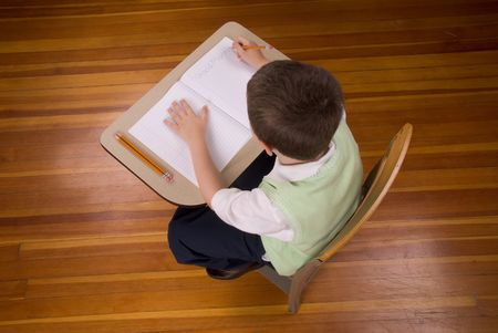 Young boy at school desk writting with book and pencils isolated over a wood floor Banco de Imagens