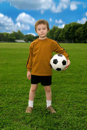 Boy with soccer ball against blue sky and green field Stock Photo - 2115569