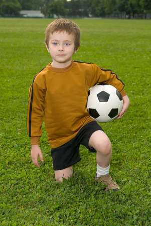 Boy with soccer ball kneeling on a green field Stock Photo - 2115571