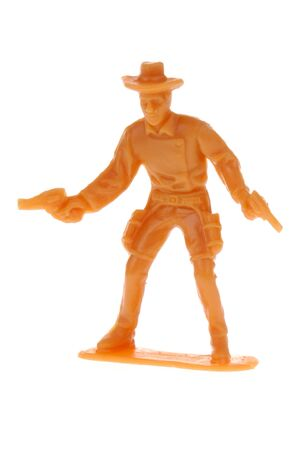 plains indian: orange plastic toy cowboy shooting pistols from the hip Stock Photo