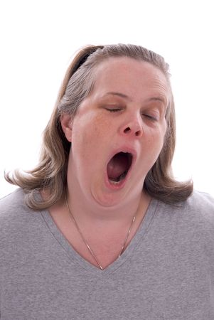 tired: Middle-aged woman yawning isolated over a white background