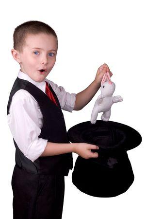 adivino: ni�o vestido como un mago tirando de un conejo de su sombrero aislados durante un fondo blanco  Foto de archivo