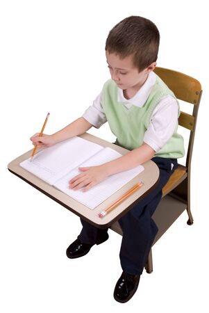 Young boy at school desk doing his schoolwork isolated over a white background Stock Photo