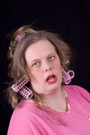 Woman wearing hair curlers and extreme makeup making a funny face isolated over black Stock Photo - 2115499