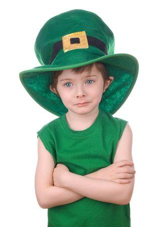 Sad young leprechaun boy wearing a humorous Saint Patricks Day hat. photo
