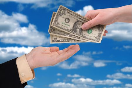 womans hand holding U.S. paper money in front of a sky background photo
