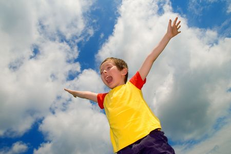 Boy with his arms wide open in front of a sky with clouds Stock Photo - 2125681