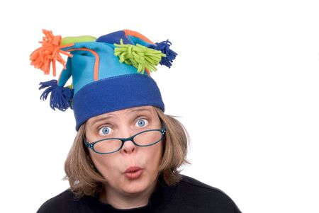 Woman wearing a funny court jester winter hat and making a funny face isolated over white photo