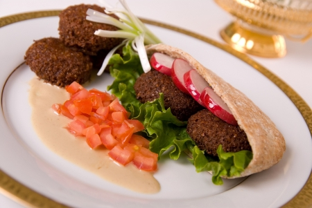 falafel in pita bread dressed on a gold lined plate with tomatoes and lettuce with a garnish
