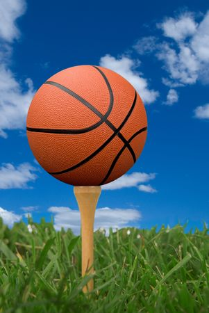 humor: Basketball on golf tee from the ground level with grass and cloudy sky