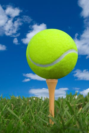 Tennis ball on golf tee from the ground level with grass and cloudy sky Stock Photo