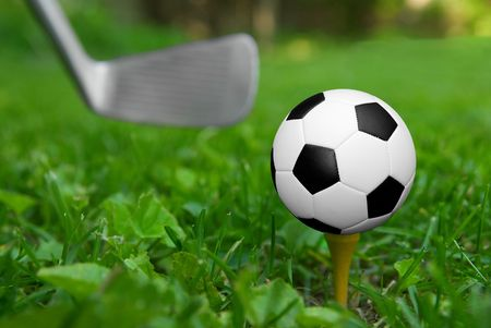 Soccer ball on golf tee from the ground level with grass and puttter