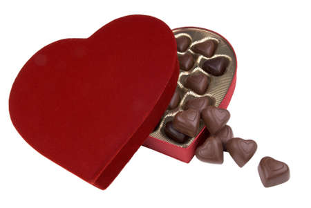 customs and celebrations: plush red velvet valentine candy box with chocolate hearts spilling out Stock Photo