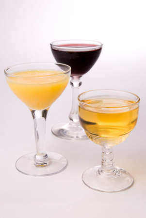 hree wine glasses with wine,orange juice and apple juice photo